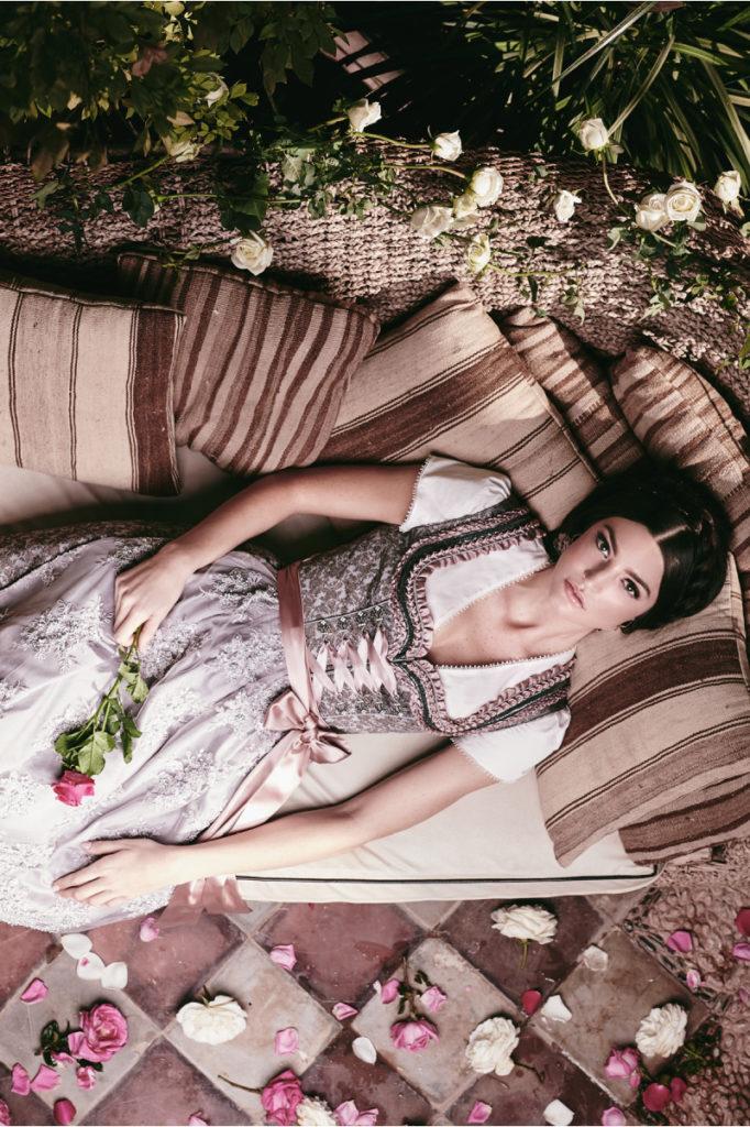 Krüger Dirndl in rosa an Frau auf Sofa liegend